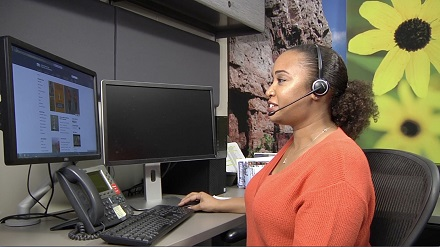 woman at computer with headset talking to a customer