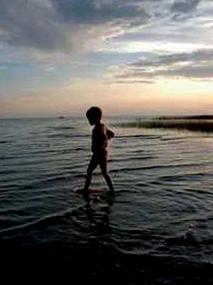 child on beach at dusk