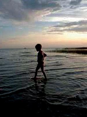 child on beach at dusk