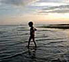 child wading in lake