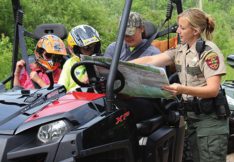 officer helping atv riders on a trail