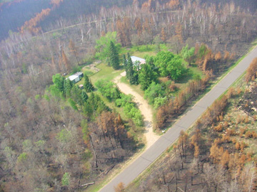 photo: aerial view showing a home that survived a wildfire