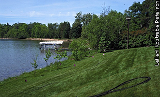 Steetar property showing mowed lawn sloping down to Sugar Lake