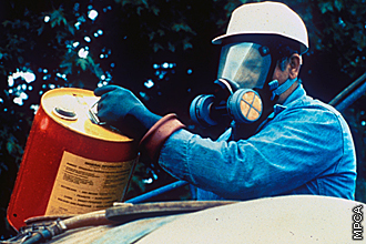 worker with mask poring chemical into sprayer