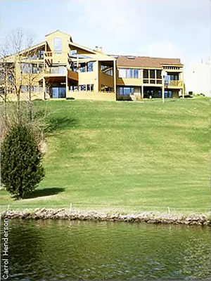 large home with very large lawn extending to edge of lake