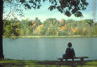 person on bench overlooking lake
