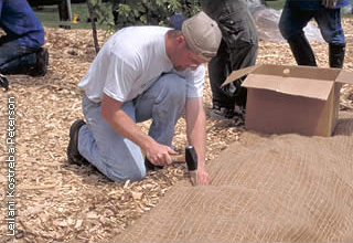 worker installing erosion control blanket