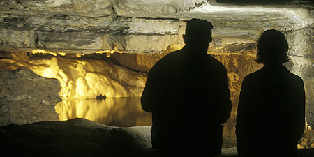 Two people silhouetted in front of cave opening