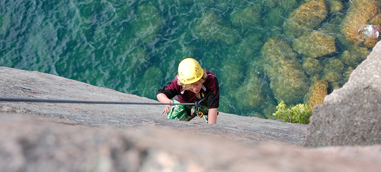 Rockclimber climbing wall above lake superior