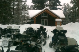 Photo of snowmobiles parked in the snow just outside the trail center.