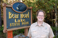 Photo of Bear Head Lake State Park Manager Jen Westlund standing next to the sign at the park's entrance.