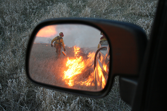 A prescribed burn reflected in a car mirror.