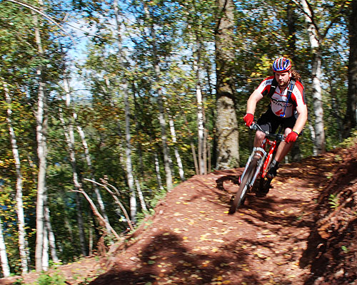 A man biking downhill on a Cuyuna Lakes mountain bike trail.