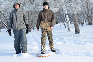 Photo of two boys snowshoeing.
