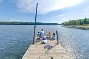 Photo of a family resting at the end of the boat dock and fishing pier at Afton State Park.
