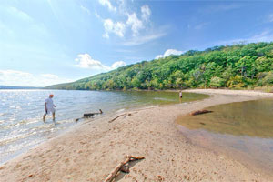 Photo of people wading along the edge of the sand bar at Afton State Park.