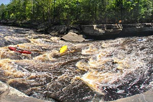 Photo of the Mother's Delight Rapids, carrying kayakers over a series of rock ledges.