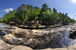 Photo of kayakers in the rushing water below the Dragon's Tooth Rapids, some of the most challenging rapids along the park.