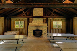 Photo of the interior of the picnic shelter which features a rock fireplace and picnic tables.