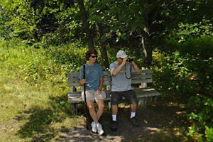 Photo of a pair of hikers enjoying the scenery of the flowing Buffalo River from a nearby bench.