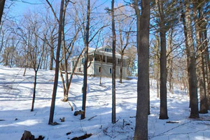 Photo of the historic Charles A. Lindbergh House, located along the snow-covered banks of the Mississippi River.