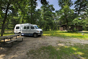 Photo of a recreation vehicle parked in the shady campground.