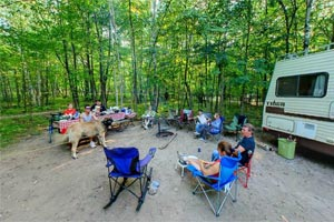 Photo of campers outside their RV at the more secluded Maple Grove Campground at Father Hennepin State Park.