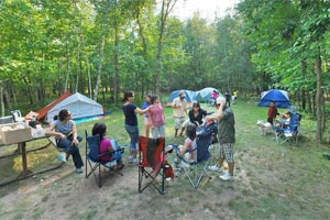 Photo of campers outside their tents at Father Hennepin State Park's group campground.