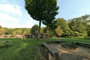 View of lawns surrounding the group center, cabins firepits and picnic tables.