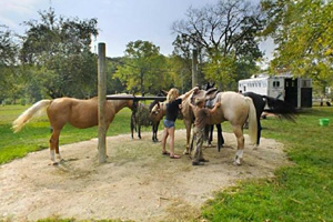 Photo of of of visitors saddling up the horses at one of the non-electric campsites located in the park.