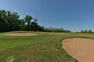 Photo of the par 3 third hole, on the the green, guarded by two bunkers.