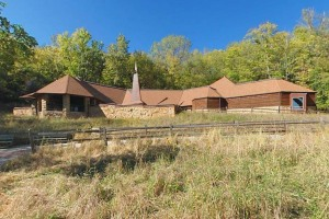Photo of the Visitor Center sitting on top of a small grassy rise backed by forest.