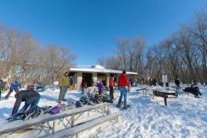 Photo of winter visitors snowshoeing outside the Picnic Island Shelter.