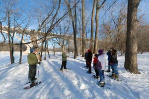 Photo of snowshoers attending a class on a snowy winter day.