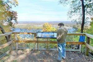 Photo of a visitor reading an interpretive panel at the North Overlook, one of the most popular places at Great River Bluffs State Park.