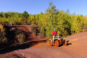 Photo of an all-terrain vehicle, the red tires coated with iron saturated soil, traveling up a hill area with different lengths and steepness to each hill.