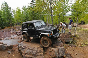 Photo of an off-road vehicle tackling the Tabletop Rock Crawl as the driver maneuvers over massive rocks laid down during the mining days.