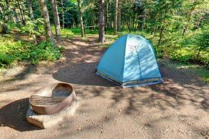 Photo of a camper's blue tent and nearby fire ring located in the park's campgrounds.
