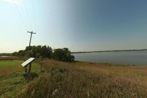 Photo of the overlook at the shore on Lac qui Parle with interpretive information of the area's geologic history.