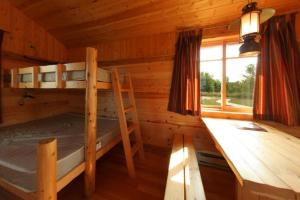 Photo of the interior of a rustic camper, featuring cabin bunks and sunlit living quarters.
