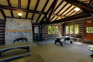 Photo of the heavy wooden beams and stone fireplace inside the historic Picnic Shelter.