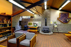 Photo of the interior of the visitor center, with a glimps of some exhibits and comfortable seating by the cozy fireplace.