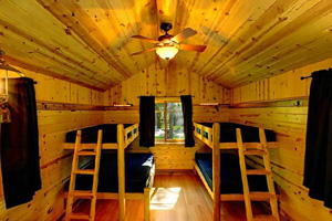 Photo of the warm pine interiors, big windows, and built-in furnishings, inside a camper cabin.