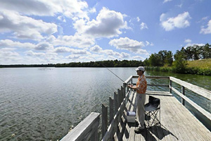 Photo of a visitor fishing on the park's wooden fishing pier along the shores of Lake Bronson.