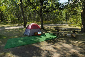 Photo of a camper's tent located at the Two Rivers Campground, next to a fire ring and picnic table.