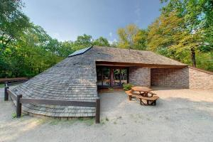 Photo of the shingled Trail Center with a patio and picnic table for visitors to rest before heading out on one of the park's many trails.
