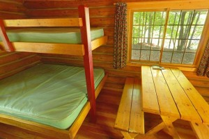 Photo of the interior of a camper cabin, showing bunks and a table.