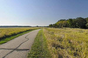 Photo of a segment of the paved Currie Loop of the Casey Jones State Trail under blue skies.