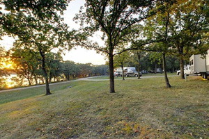 Photo of a campground shaded by an old-growth oak canopy with views of Lake Shetek.