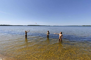 Photo of visitors playing Frisbee in the park's swimming area.